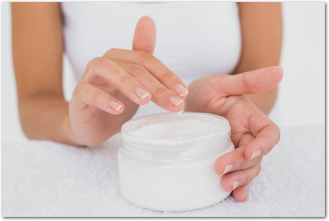 Close up mid section of woman applying cream over white background